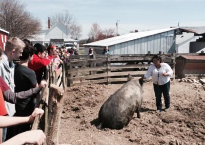 Kim Gore feeding a happy pig during a school field trip